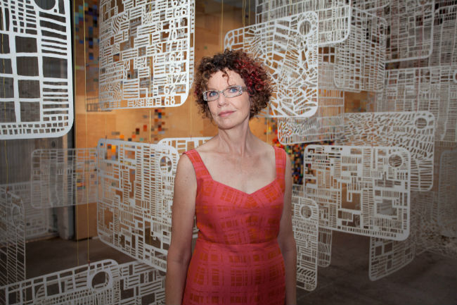 "Arist Laurie Frick stands in front of her installation, ""Quanitfy Me,"" made of 96 laser-cut drawings."